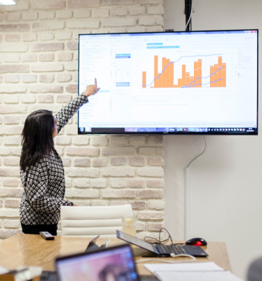 person pointing to screen with data chart